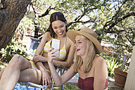 Two happy young women in garden sharing cell phone - WESTF23225