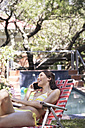 Young woman on the phone in deckchair at the poolside - WESTF23231