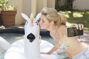 Young woman taking cell phone picture with unicorn in swimming pool - WESTF23243