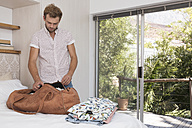 Young man packing bag in bedroom - WESTF23264