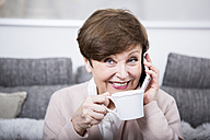 Portrait of a senior woman using smart phone, drinking coffee - WESTF23285