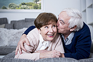 Senior couple lying on couch, hugging and kissing - WESTF23306