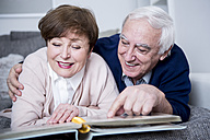 Senior couple lying on couch, looking at photo album - WESTF23309