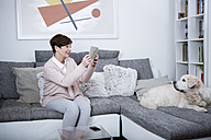 Senior woman sitting on couch taking pictures of her dog - WESTF23312