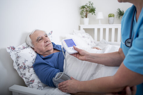 Gereatric nurse measuring blood pressure of patient, lying in bed - WESTF23354