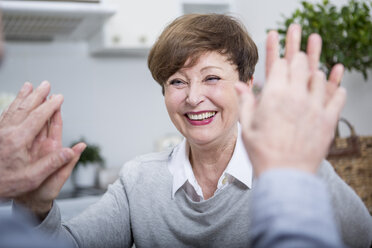 Smiling senior woman giving man high five - WESTF23372
