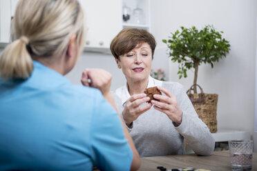 Gereatric nurse doing dexterity games with elderly patient - WESTF23375