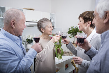 Two senior couples celebrating, toasting with red wine - WESTF23378