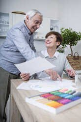 senior woman painting with crayons, husband watching - WESTF23393