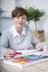 Senior woman drawing picture with crayons - WESTF23396