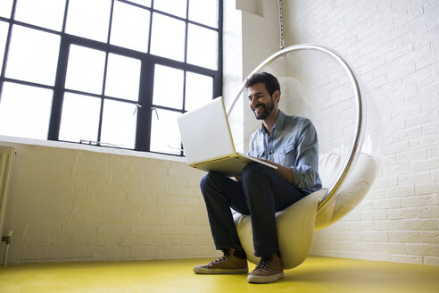 Smiling man sitting on swing in his loft using laptop - ABZF02041