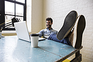 Smiling man sitting with feet up at desk looking at laptop - ABZF02059