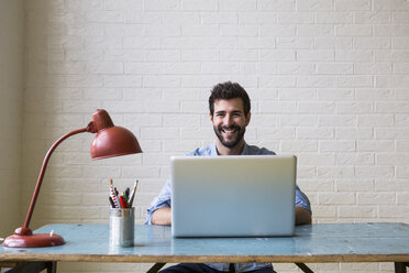 Portrait of happy young man sitting at desk working with laptop - ABZF02068