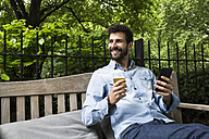 Portrait of smiling young man with cell phone and glass of beer relaxing in garden - ABZF02077
