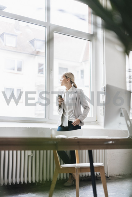 Businesswoman in the office looking out of window - JOSF01057 - Joseffson/Westend61