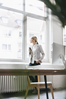 Businesswoman in the office looking out of window - JOSF01057