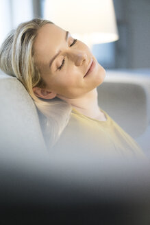 Portrait of blond woman with eyes closed relaxing on couch - JOSF01066