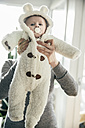 Mother holding up baby in a polar bear costume - MFF03596