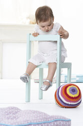 Baby girl sitting on chair looking down - FSF00917