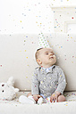 Portrait of baby boy with eyes closed wearing paper hat - FSF00926