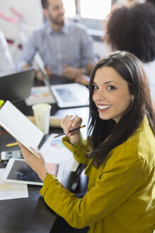 Portrait of smiling businesswoman during a meeting in office - GIOF02640