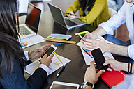 Business people using cell phones during a meeting in office - GIOF02652