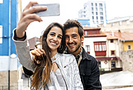 Smiling couple taking a selfie in the city - MGOF03405