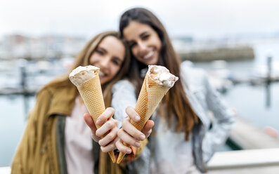 Two young women having fun with icecream - MGOF03411