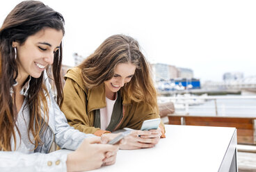 Two happy young women sending messages with their smartphones - MGOF03420