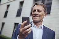 Portrait of smiling mature businessman outdoors with earphones and smartphone - MFF03609