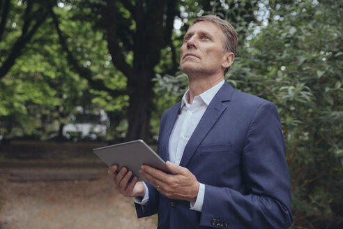 Mature businessman standing at trees holding tablet - MFF03612