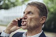 Portrait of angry mature businessman outdoors on the phone - MFF03618