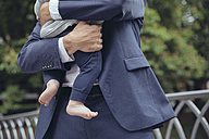 Businessman clutching baby boy outdoors - MFF03621