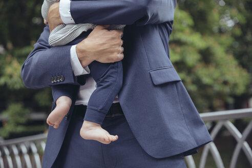 Businessman clutching baby boy outdoors - MFF03621