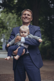 Portrait of smiling mature businessman holding baby boy outdoors - MFF03624