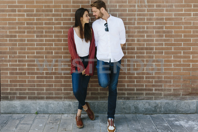 Happy couple standing in front of brick wall - GIOF02711