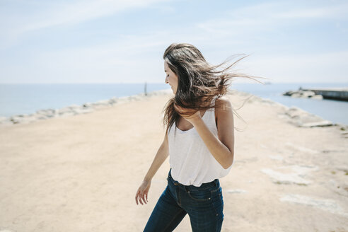 Young woman standing on the beach, enjoying wind - GIOF02729