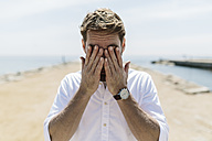 Mid adult man on the beach covering eyes - GIOF02732