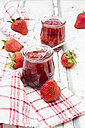 Two glasses of homemade strawberry jam, kitchen towel and strawberries on white wood - LVF06153