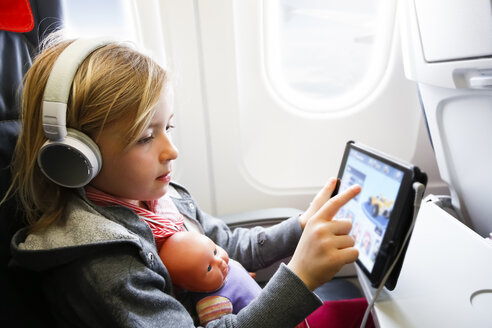 Little girl sitting on an airplane watching something on digital tablet - FKF02331