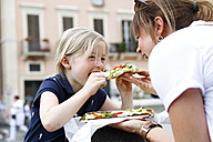 Italy, mother and little daughter eating Pizza together - FKF02337