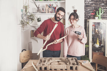 Young couple assembling flat-pack stool at home - RTBF00887