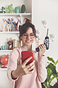 Portrait of smiling young woman taking selfie with electric screwdriver at home - RTBF00890