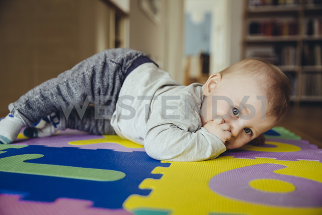 Portrait of baby boy with finger in his mouth lying on the floor in the living room - MFF03628