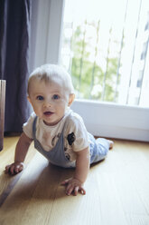 Portrait of baby boy crawling on the floor - MFF03637