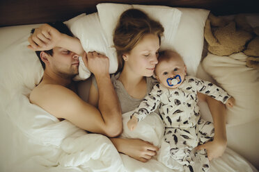 Mother, father and baby boy cuddling in bed - MFF03643