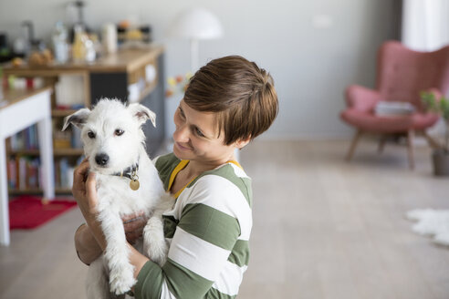 Woman holding dog on her arms at home - RBF05671