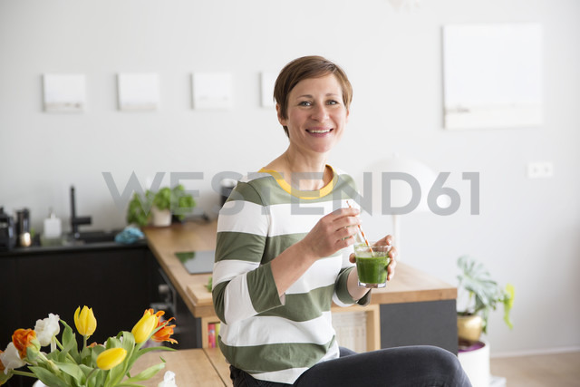 Portrait of smiling woman with green smoothie in the kitchen - RBF05680