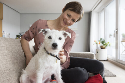Woman and her dog sitting together on the couch - RBF05686