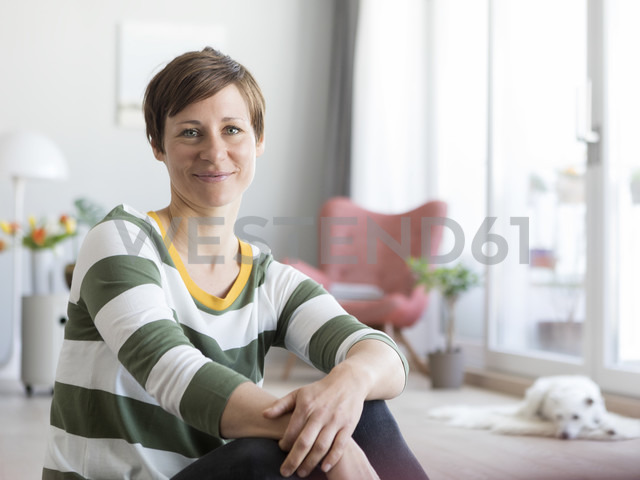 Portrait of smiling woman sitting on the floor in the living room - RBF05692 - Rainer Berg/Westend61